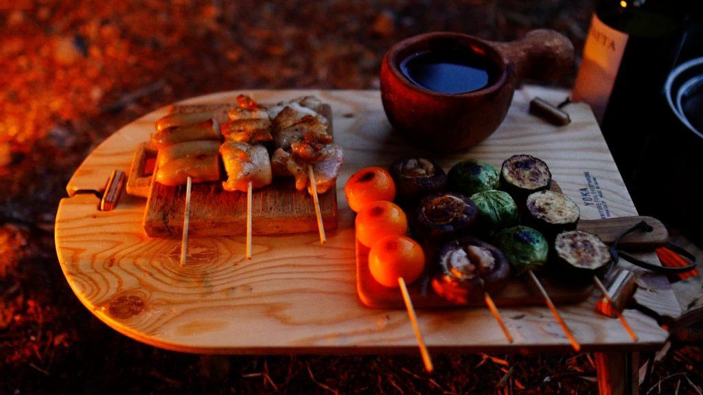 ミニテーブルTRIPOD TABLE SOLOの上に串焼きを盛り付け。